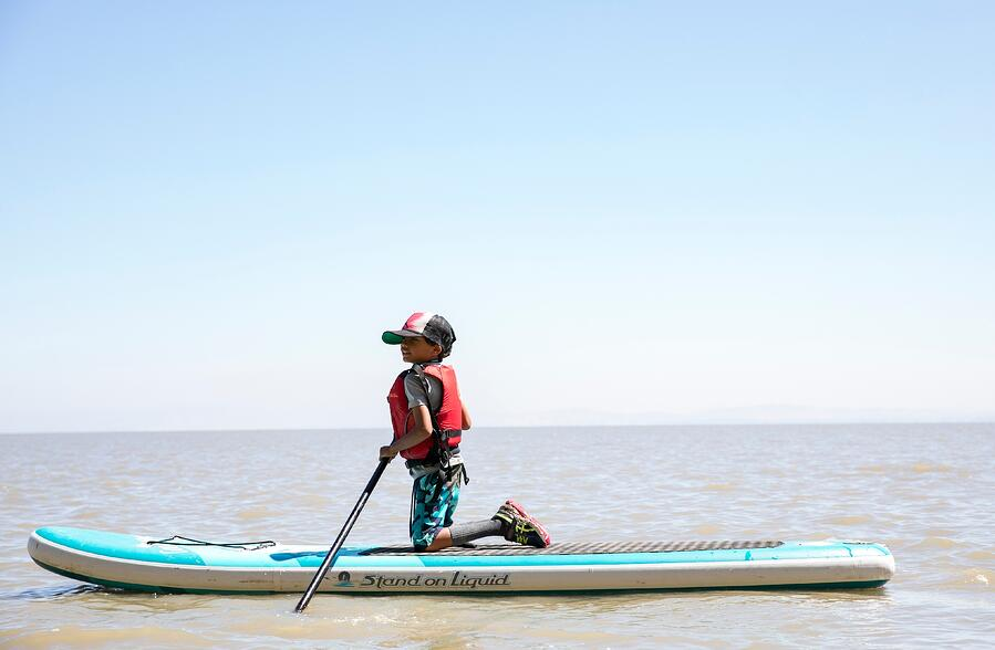 young kid stand up paddleboarding in the Bay Area of California