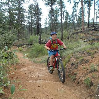 Boy biking down trail.jpg