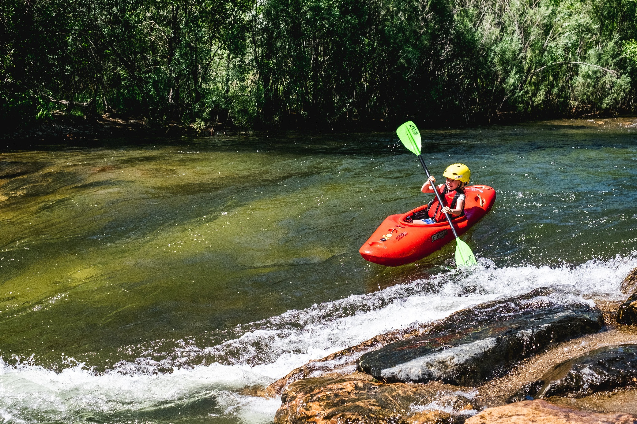 young girl whitewater kayaking about to reach a rapid