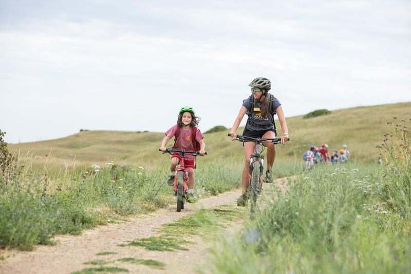 kid biking with his instructor at boulder summer camp