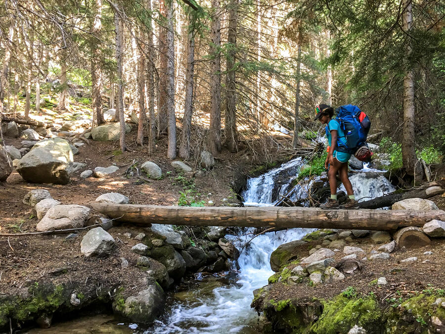 teen crossing a river while backpacking in the mountains