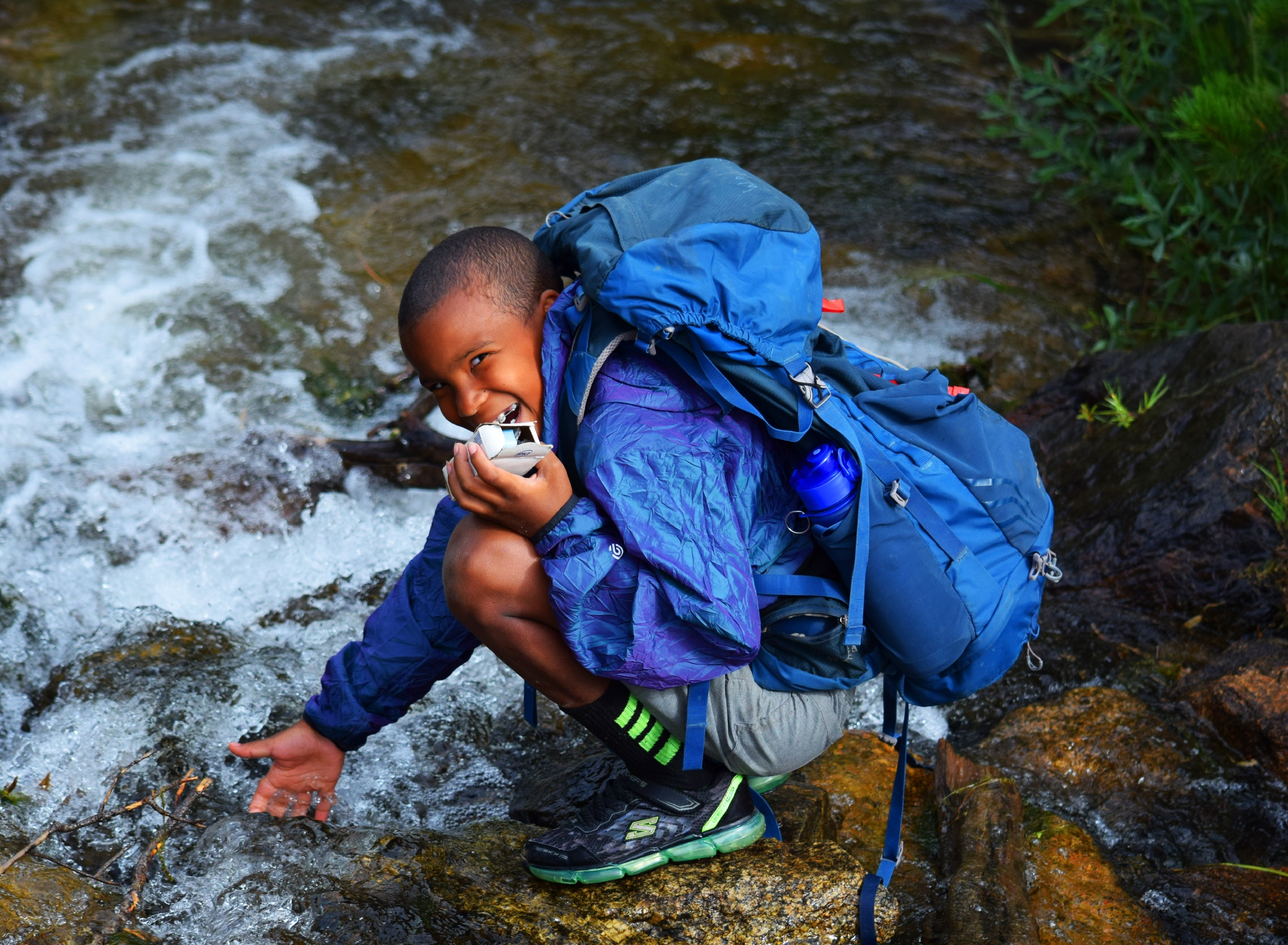 kid smiling near river on backpacking trip